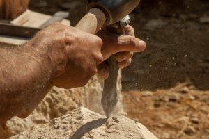 Guédelon: Ein Steinmetz behaut einen Mauerstein.