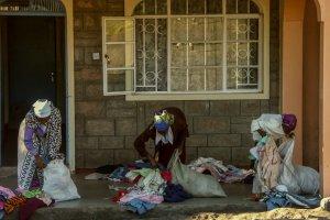 Mitarbeiter der Mully Children's Family sortieren Kleidungsstücke einer Spendenlieferung.